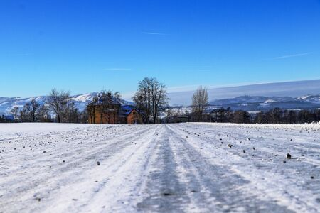 Frozen forest road sprinkled with gravel in foothills of Beskydy mountains in Czech republic. Typical winter day. Countryside view. Gorgeous snow cover