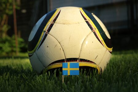 Simple two-colour national flag of Sweeden on wooden stick with soccer ball in background. Soccer championship 2022. Stok Fotoğraf