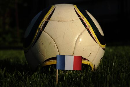 Soccer championship 2022.   National flag of France on wooden stick in grass with typical soccer ball in background. Self-worth. Tricolour which means everything for french people.