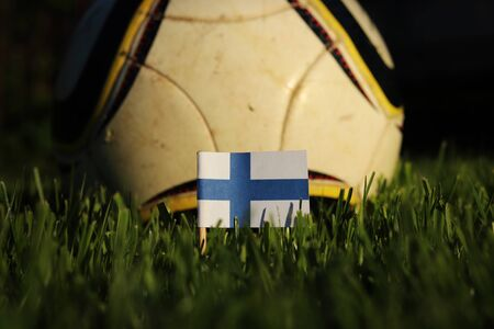Finland flag stick to grass with football ball in background. Soccer championship 2022.  Blue and white paper on wooden stick. Finnish state symbol. International action. Stok Fotoğraf