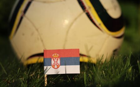 Flag of Serbia between stems of grass and in the background wonderfull classic ball. World Championship 2022.     Serbian state symbol. International match.
