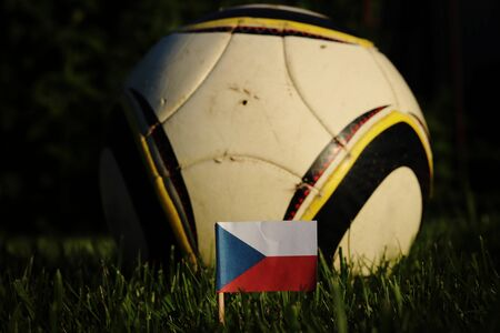 State symbol of Czech republic in grass with soccer ball in background. National czech flag with three colours. Blue, red and white. Championship 2022.
