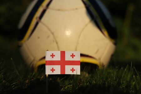 National flag of Georgia on wooden thick stick stabbed in soccer field and in the background classic football ball. World Championship 2022.