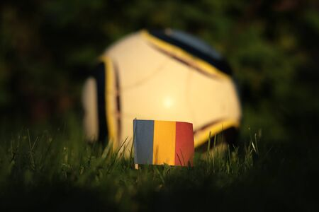 Flag of Romania on wooden stick at sunset. World Championship 2022.   Classic and casual soccer ball for everyone. Romanian soccer team is ready for match. Stockfoto