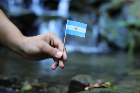 Argentina in the hands of powerful people. Young man holds flag of Argentina near stream. Concept of humanity and dominance. Prove of depraved and avariciousness. Colour man waves with flag.