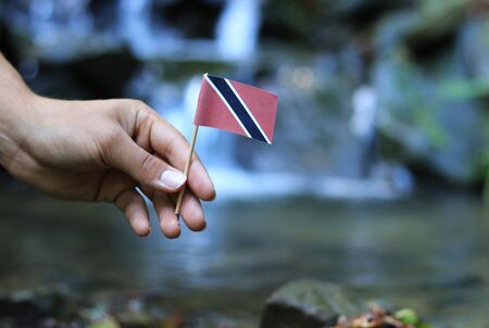 Poor land Trinidad and Tobago in the hands of affluent people. Young man holds flag of Trinidad and Tobago near stream. Concept of humanity and dominance. Prove of depraved and avariciousness.