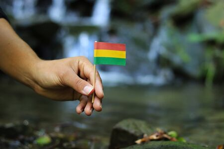 Poor Bolivia in the hands of powerful people. Young man holds flag of Bolivia near stream. Concept of humanity and dominance. Prove of depraved and avariciousness. Problems with drogs.