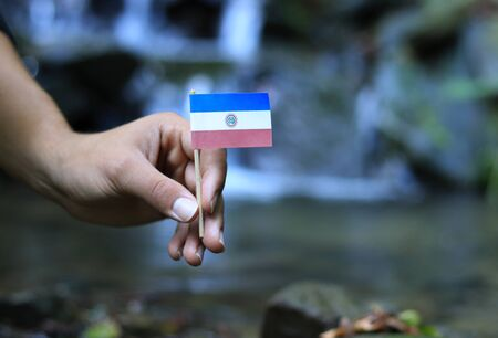 Poor Paraguay in the hands of powerful people. Young man holds flag of Paraguay near stream. Concept of humanity and dominance. Prove of depraved and avariciousness. Colour man waves with flag.