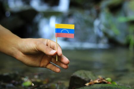 Poor Venezuela in the hands of powerful people. Crooked man holds flag of Venezuela near stream. Concept of dominance and criminality. Prove of depraved and avariciousness. Problems with drogs Фото со стока