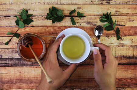 Tasty herbal tea for sickness and fight verus flu. Mint leaves, honey with spoon and cup of hot tea. Sick man warm his hands on a cup. Concept of herbalism and modern apothecary.
