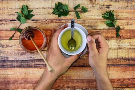 Sick man holds hot herbal tea for warms hands. Good raws also is brown honey, mint leaves and important allowance lemon. Modern apothecary, self-care, immunity. Basic things for sickness.