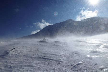 Whirlwind on snowy hilss in Slovakia Low Tatras. Epic wind storm in january with clear sky. Frozen land and snow attack on skier from side. Unpleasant side wind 스톡 콘텐츠