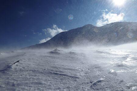 Wirbelwind auf verschneiten Hügeln in der Slowakei Niedere Tatra. Epischer Windsturm im Januar mit klarem Himmel. Gefrorenes Land und Schnee greifen Skifahrer von der Seite an. Unangenehmer Seitenwind