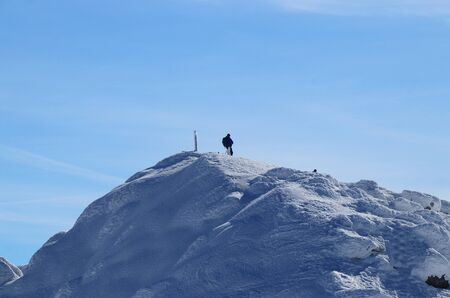 Lone wolf on the peak of Chopok in Low Tatras in Slovakia, Europe. Snowy hill and man with rucksak stands and enjoy views to the valley and paradise blue sky. Concept of wildness and freedom.
