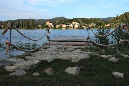 Wooden molo with ropes as protected opposite fall down. Part of specific nature in Split-Dalmatia County, Croatia. Morning times near water. Ideal time for rest or relax.