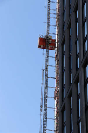 Unusual outdoor lift for work at high altitudes. Typical transport for works on reconstruction skyscrapers. Construction between street in the middle of London. We need repair it.