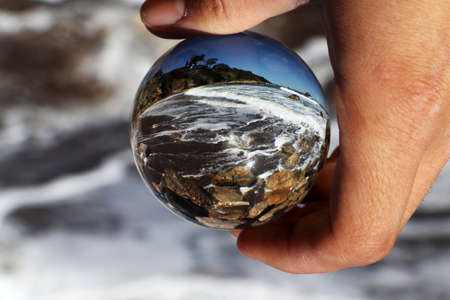 Through lens ball watchs rough sea, tides and foamed water as it smashes against the rocks. Piece of famous beach Baths Of Aphrodite. Piece of nature Cyprus in glass ball. 版權商用圖片