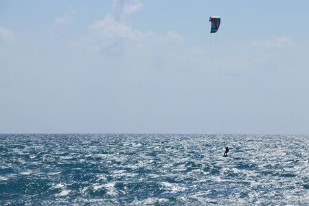Kiteboarding is an action sport combining aspects of wakeboarding, snowboarding, windsurfing, surfing, paragliding, skateboarding and sailing into one extreme sport. Kiteboarder in Mediterranean sea. Stock Photo