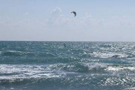 Kiteboarder is pulled across water by a power kite in Cyprus, Europe near famous Pissouri beach. Wonderful day with water activity. Active lifestyle. Special sport for connoisseur, gourmet.