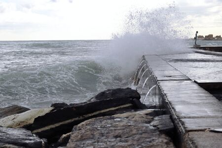 Large wave crashed against flood walls on a beach near Paphos, Cyprus. The sea awoke and showed its unpredictability and strength. Summer vacation. Idyllic moment