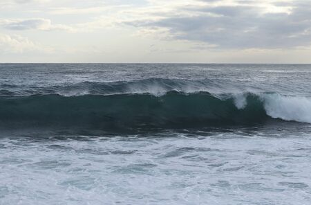 Close up of sea level while creating the perfect wave for surfers. The wave begins to flip and fall to the rest of the sea level. Stormy sea after a strong wind. Paphos, Cyprus. 版權商用圖片