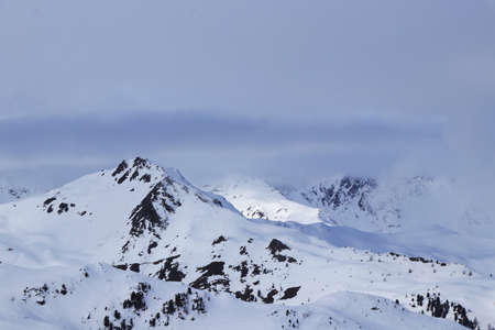 View on snowy mountains peaks as Hochhorn, Corno di Fana and Monte della Chiesa from Ski resort Sillian - Thurntaler in Tirol, west Austria. Mountains peaks are lost in fog.