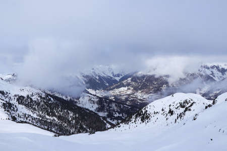 View of the snowy Villgratental valley between Austria Alps in Tyrol in western Austria. The peaks of these 2,000-meter mountains are lost in fog and thick clouds. Ski resort Sillian. Stock Photo
