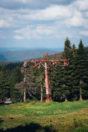 Old rusty ski lift standing on the top of Vysoka hole in Hruby Jesenik, in the Czech mountains on the border with Poland. Abandoned ski transport facility. Nature reserves in the Czech Republic. Stock Photo