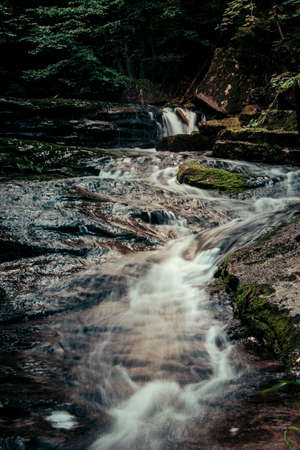 Small river in a dark forest is looking for a way through a rock. The rainy season in the Jizera Mountains on the land with Poland. Czech nature treasure. Europe beautiful places.