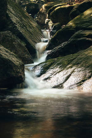 Slowly flowing narrow stream and four-stage waterfalls from the Jizera Mountains, a treasure trove of Czech nature on the border with Poland.