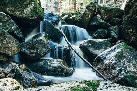 Slowly flowing stream and waterfalls in Jizera Mountains, Czech Republic. Water flows from all cracks of stones and rocks. Source of drinking water.