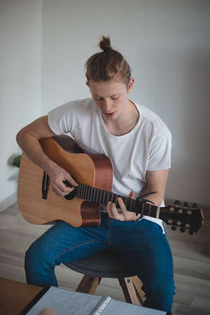 focused young singer while singing and playing guitar in an afternoon idyll. A common portrait of a man in daily activity. Boy aged 20-29 playing guitar.