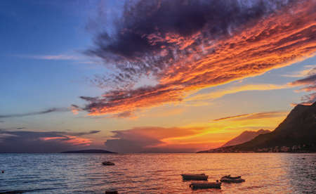 Fairy-tale sunset setting over the foot of the mountain. The sun reflects off the surface of the Mediterranean Sea and illuminates small boats that swim in an indefinite direction. Gradac, Makarska, south of Croatia. Dream holiday Stock fotó