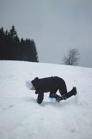 Athlete falls from a plastic snowboard and falls hard on the snow and sprawls. The boy's board got stuck and it threw him out and he did a somersault. Hard landing on the piste. Dangerous fall.