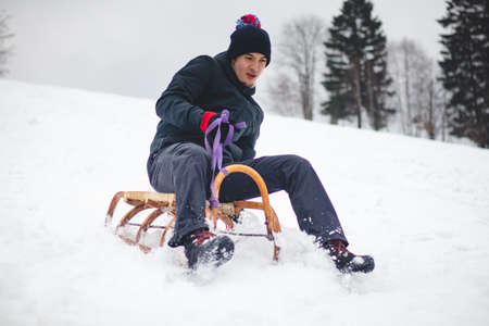 Adult man in winter black clothes rides at high speed on a wooden sledge and tries not to fall off it. Foot braking. Use of fresh powder for a fast ride. Winter season in the Czech Republic.