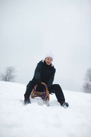 Joyful smile of a young sixteen year old boy riding a historic wooden sled on a ski slope. Dangerous driving. Enjoying the fallen snow in winter. Fooling around at a young age. Immortality.