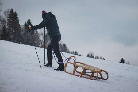 Climber pulls to the top of a wooden sled to ride on the piste. Pause for rest. Candid portrait of a man pulling a sledge, which he has hooked behind his body and helps himself with trekking poles.