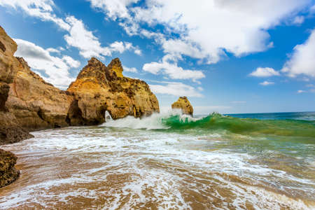 Waves crashing on the rocks at Praia Dos Tres Irmaos near Portimao, in Algarve region, Portugal