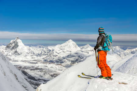 Athletic man skiing on a sunny day with beautiful view of Matterhorn in the background