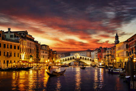 Ponte Rialto and gondola on water reflecting sunset colors in Venice, Italy