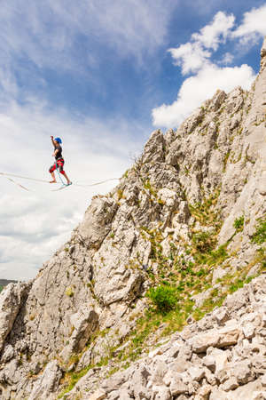 Young slackliner man balancing on a slackline betweend two rocks. Highline with a beautiful natural landscape behind Stok Fotoğraf