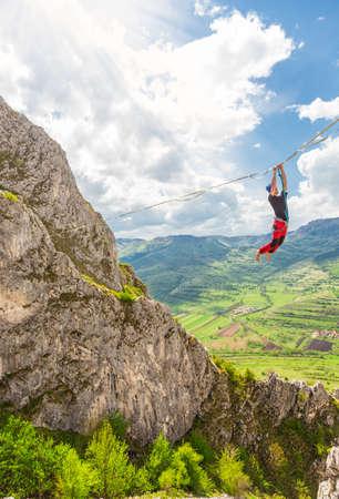 Young slackliner man hanging on a slackline betweend two rocks. Highline with a beautiful natural landscape behind