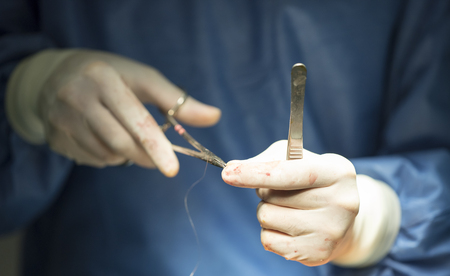 surgeons hands holding a needle and thread and a needle holder