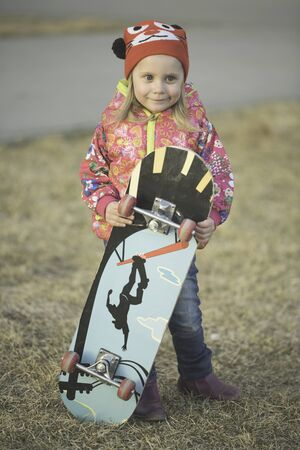 Little girl is standing on grass with skateboard
