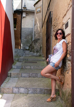 woman leaning against a wall in a typical Asturian street