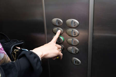 woman inside an elevator pressing a button