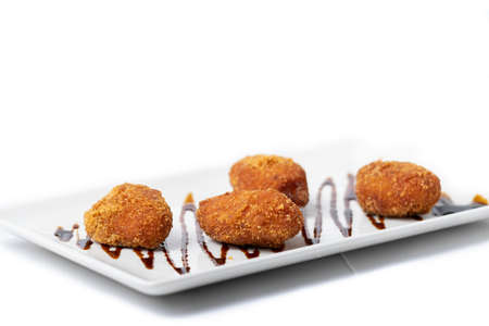 assortment of croquettes on a white rectangular plate