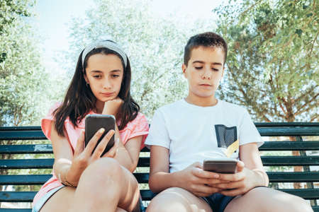children looking at a cellphone sitting on a bench in the park