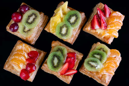 puff pastry with tangerine, kiwi and strawberry fruit on black background viewed from above