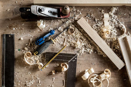 Workbench with a variety of hand tools in a woodworking or cabinetmaking workshop including chisels, screwdrivers, tape measure, pencil, ruler Stock Photo